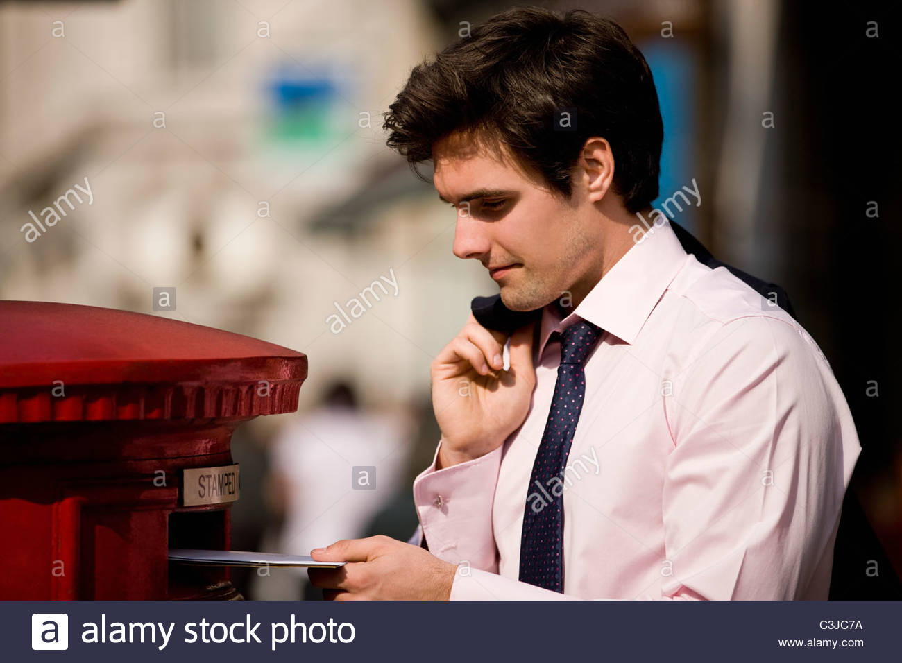 A businessman posting letters in a letterbox - Stock Image
