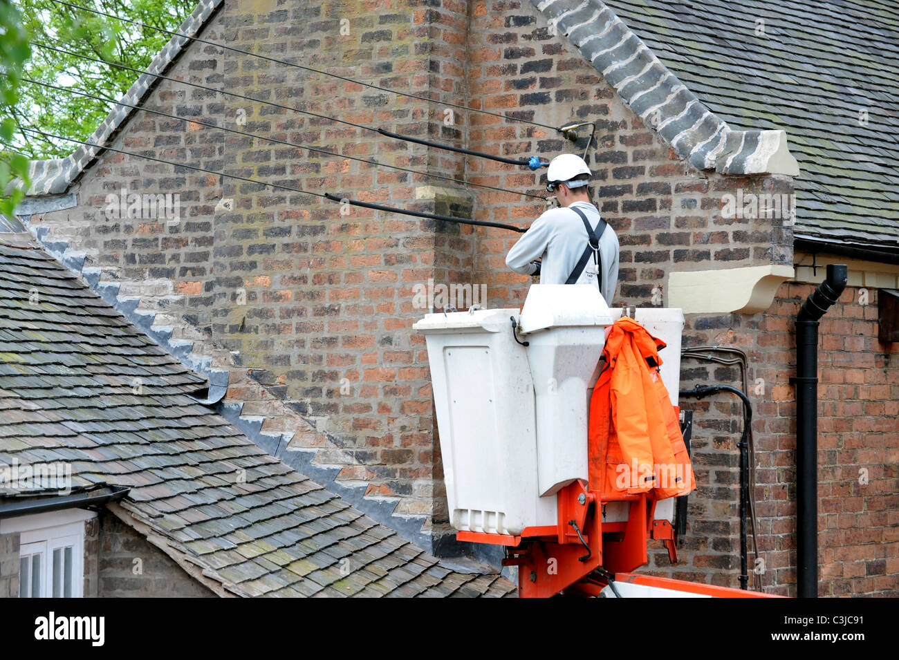 Electrical conractor repalcing old external cables on old house UK - Stock  Image