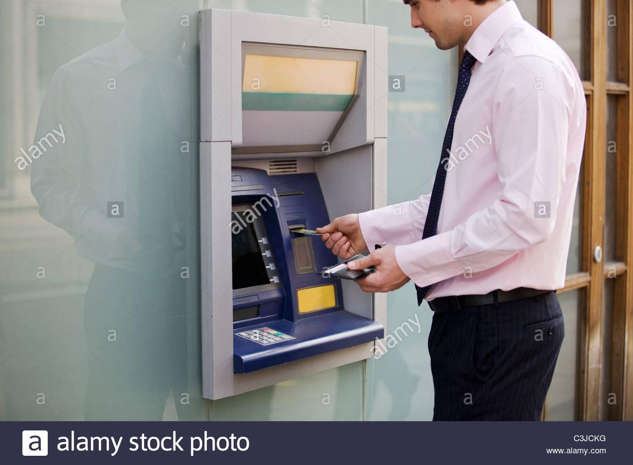 A businessman using a cash machine - Stock Image