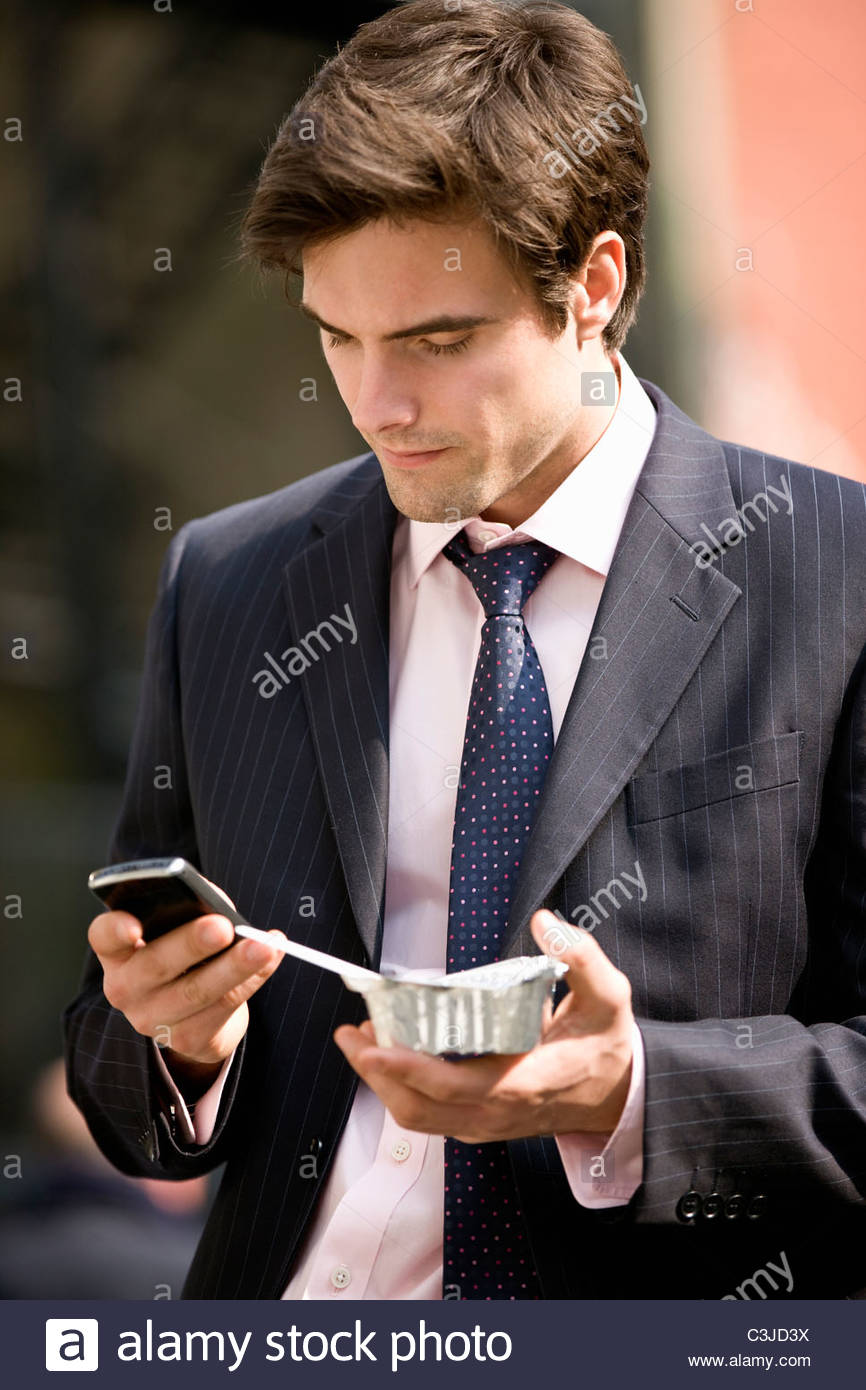 A businessman using his mobile phone, eating take-away food - Stock Image