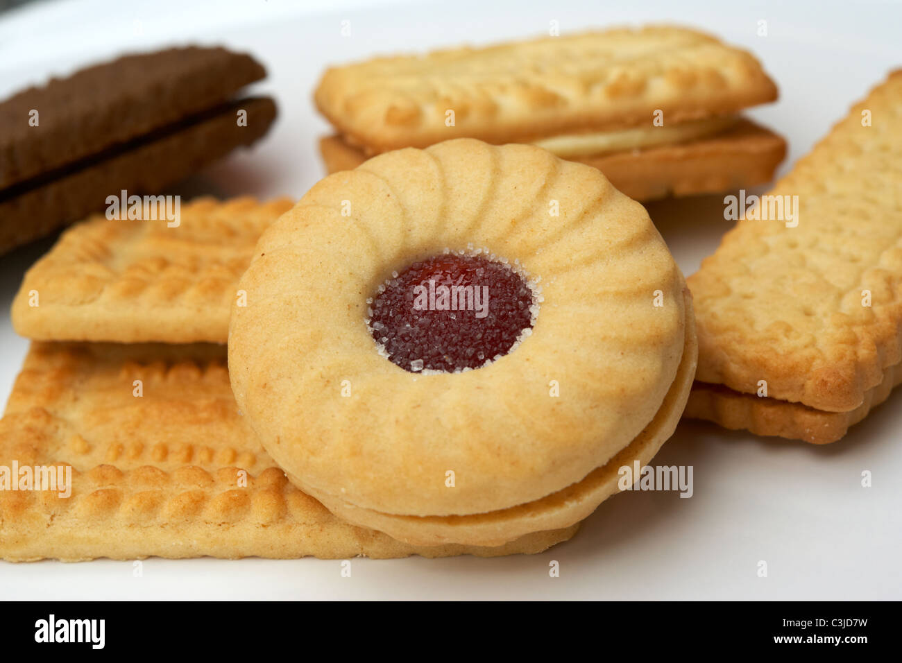 assorted british biscuits on a plate including a jammie dodger - Stock Image