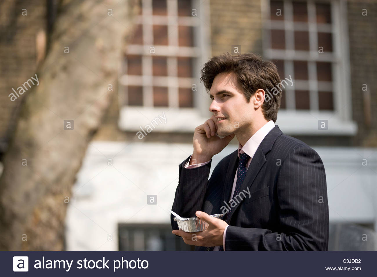A businessman talking on his mobile phone, eating take-away food - Stock Image