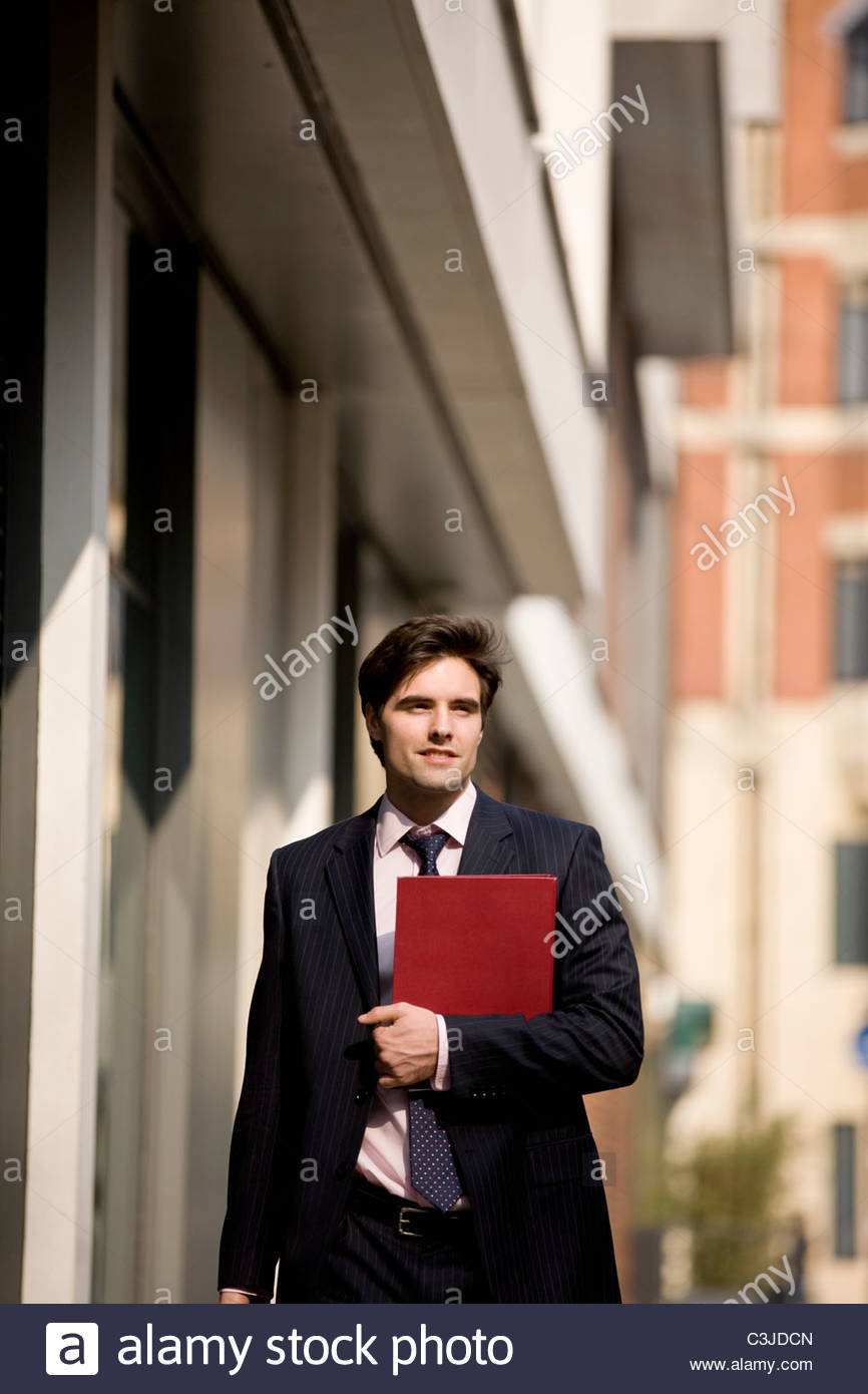 A businessman walking along the street, holding a folder - Stock Image