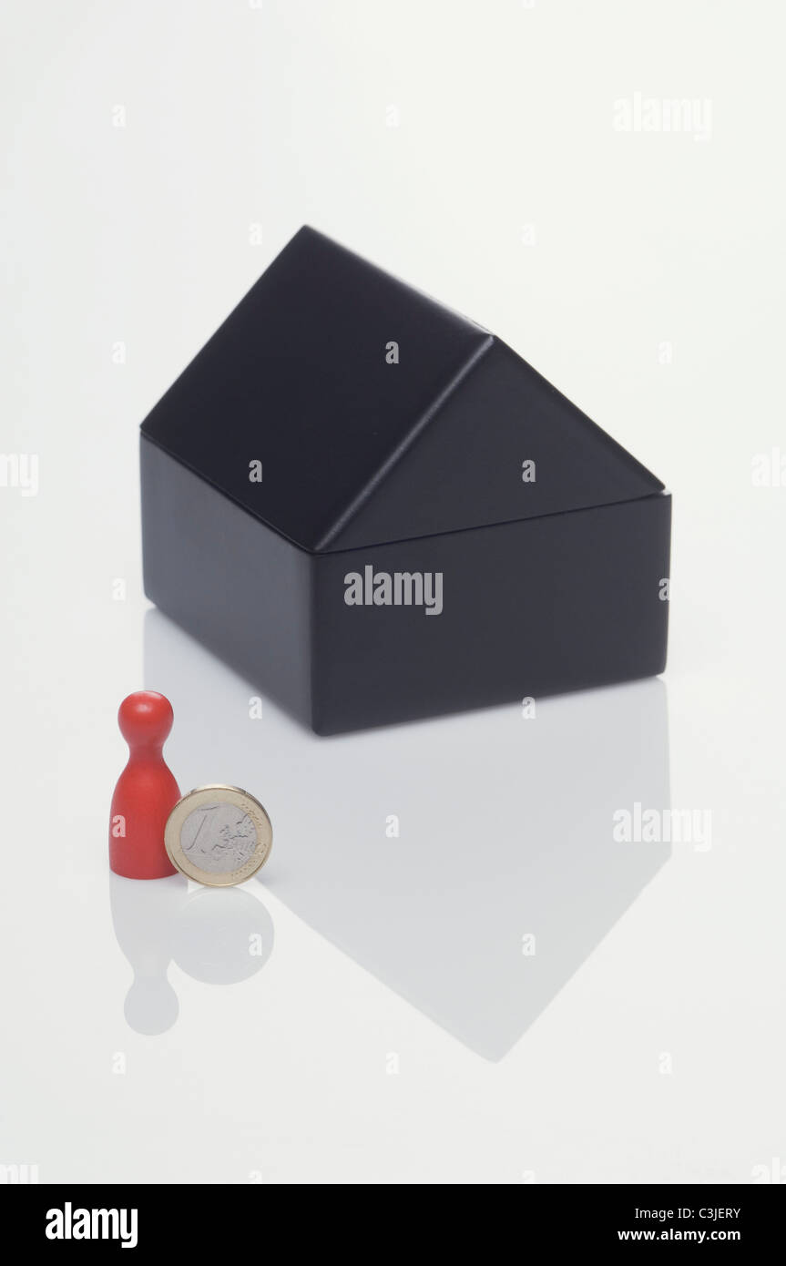 Miniature house, euro coin and pawn on white background - Stock Image