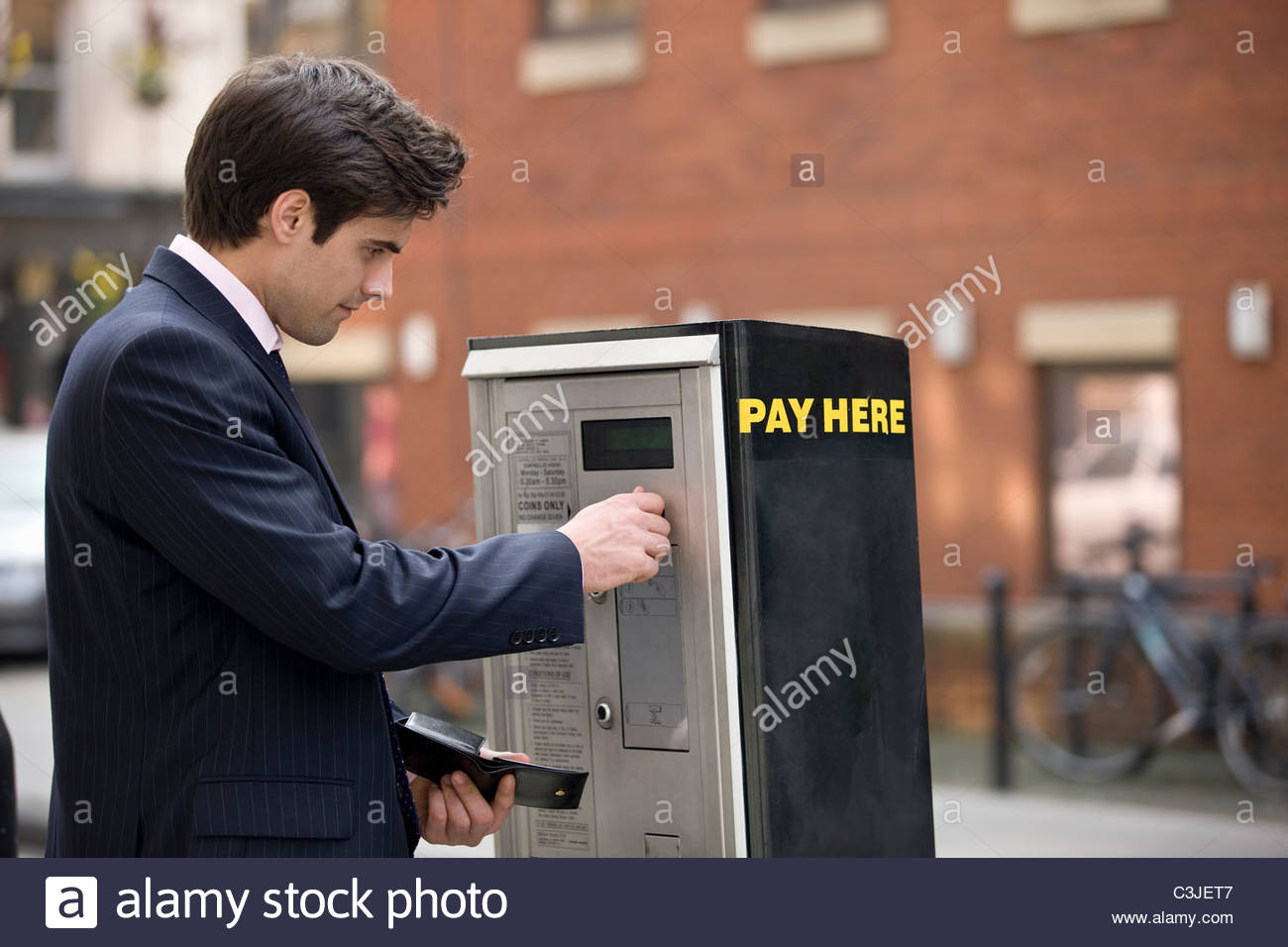 A businessman putting coins in a parking meter - Stock Image