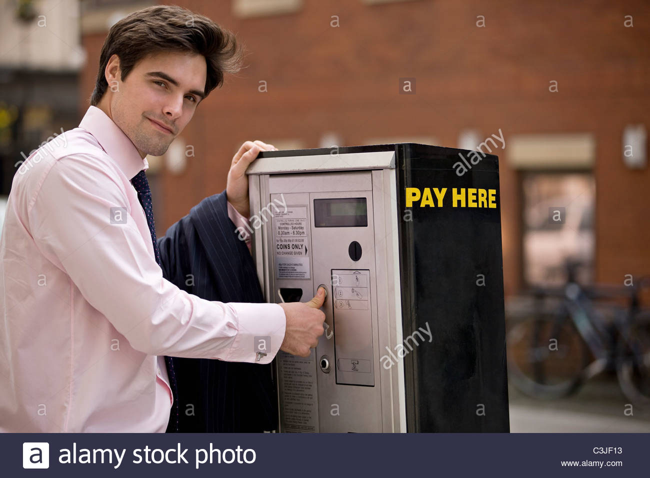 A businessman buying a ticket from a parking meter - Stock Image