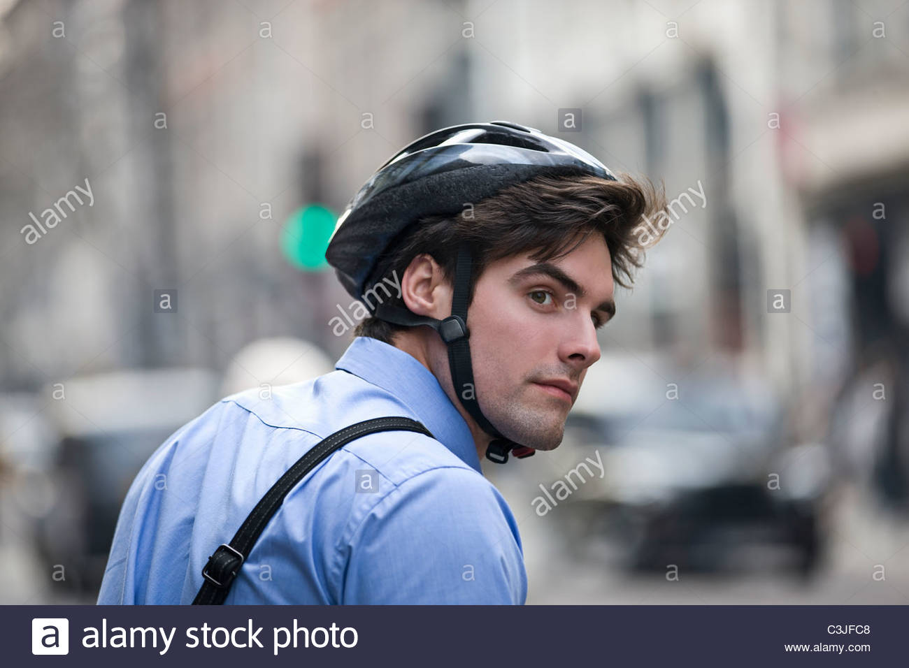 A businessman wearing a cycling helmet, commuting to work - Stock Image
