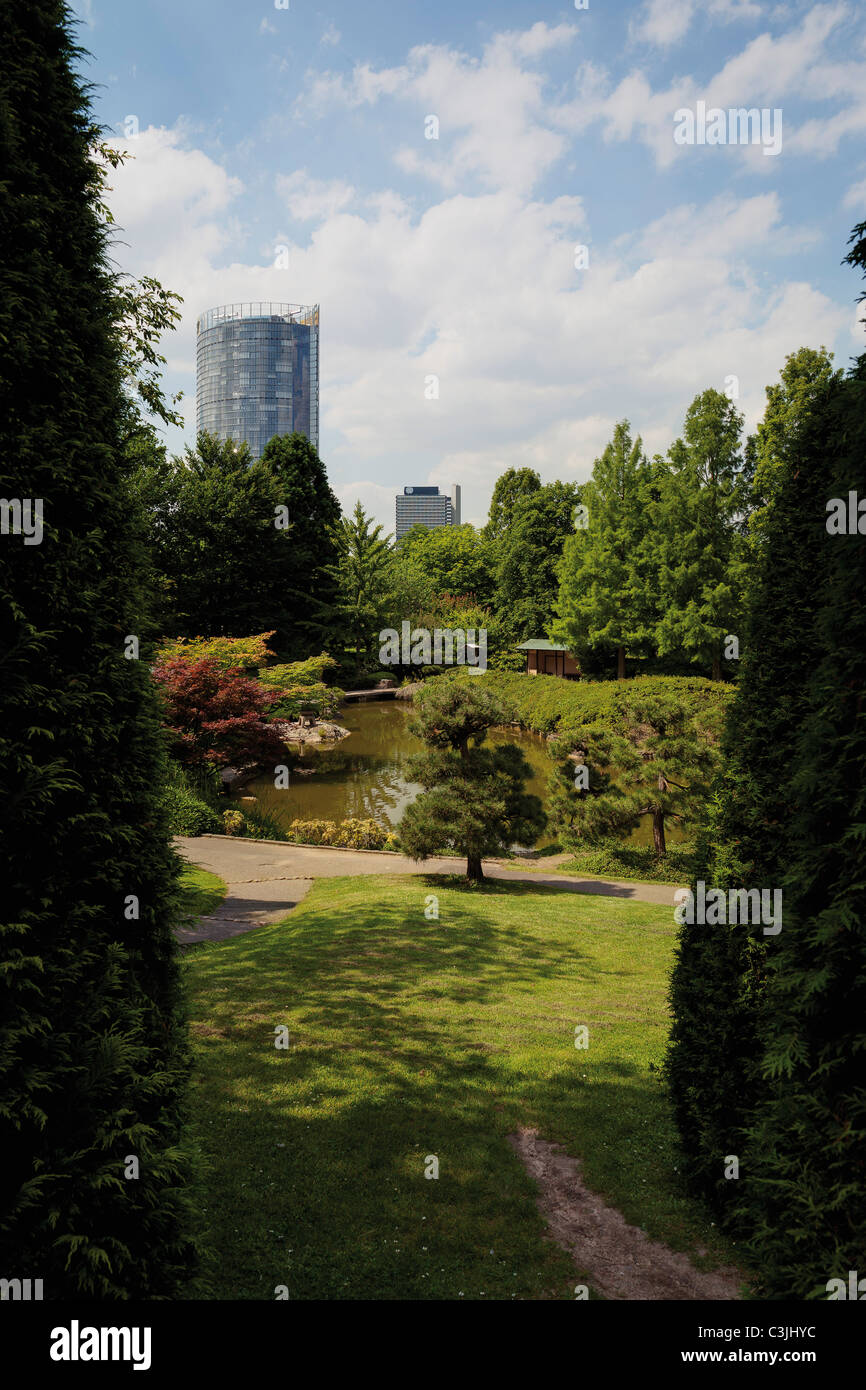 Germany, North Rhine-Westphalia, Bonn, View of Japanese garden with skyscraper in background - Stock Image