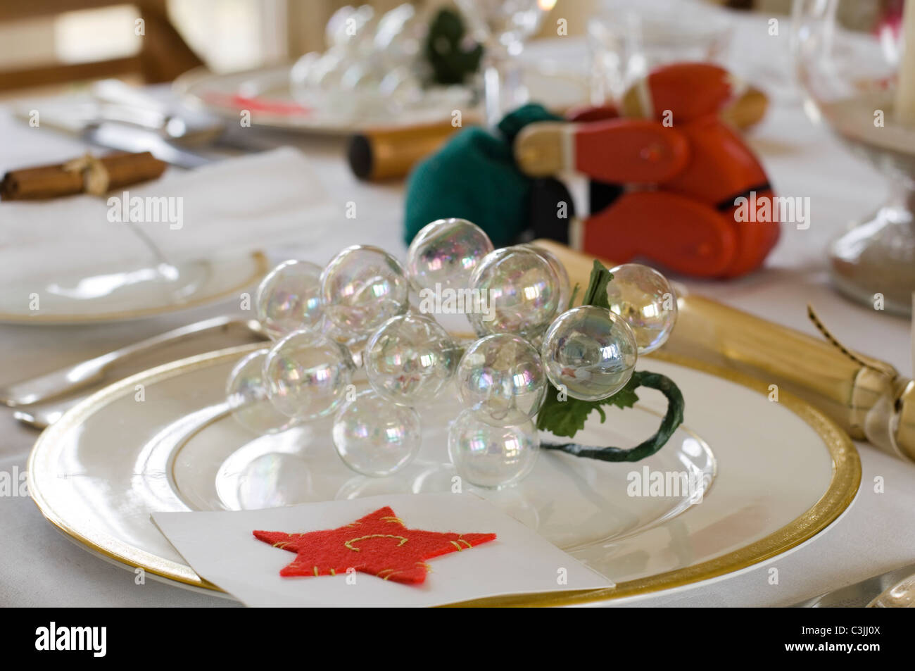Festive table place setting with cracker and glass baubles - Stock Image