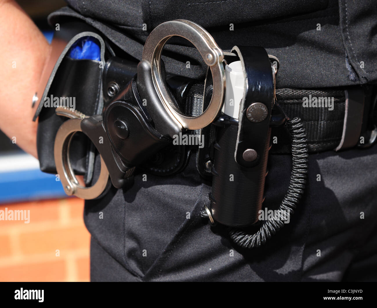 Detail of police utility belt worn by british police, showing handcuffs and CS gas spray. - Stock Image