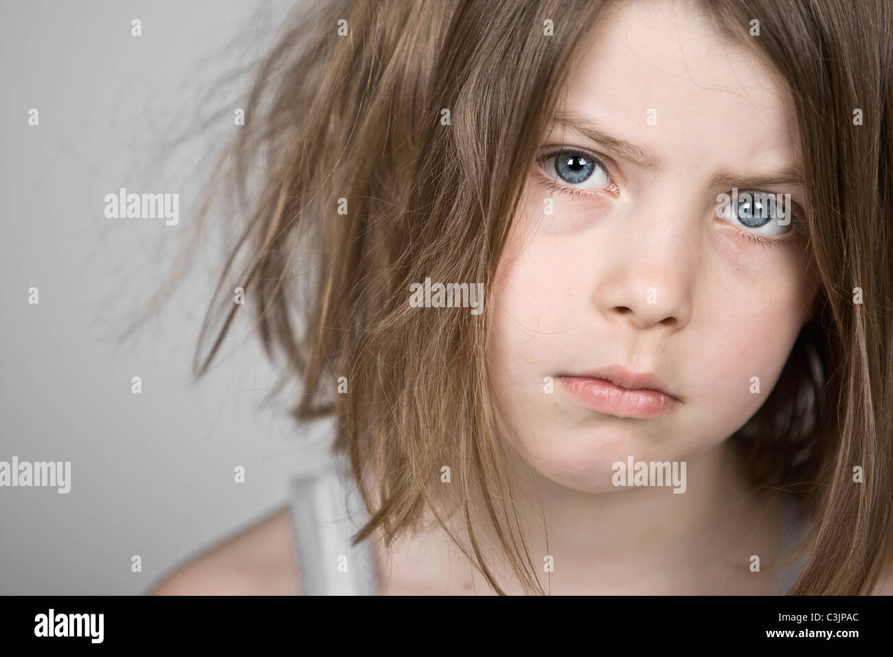 Studio portrait of sad girl (6-7) - Stock Image