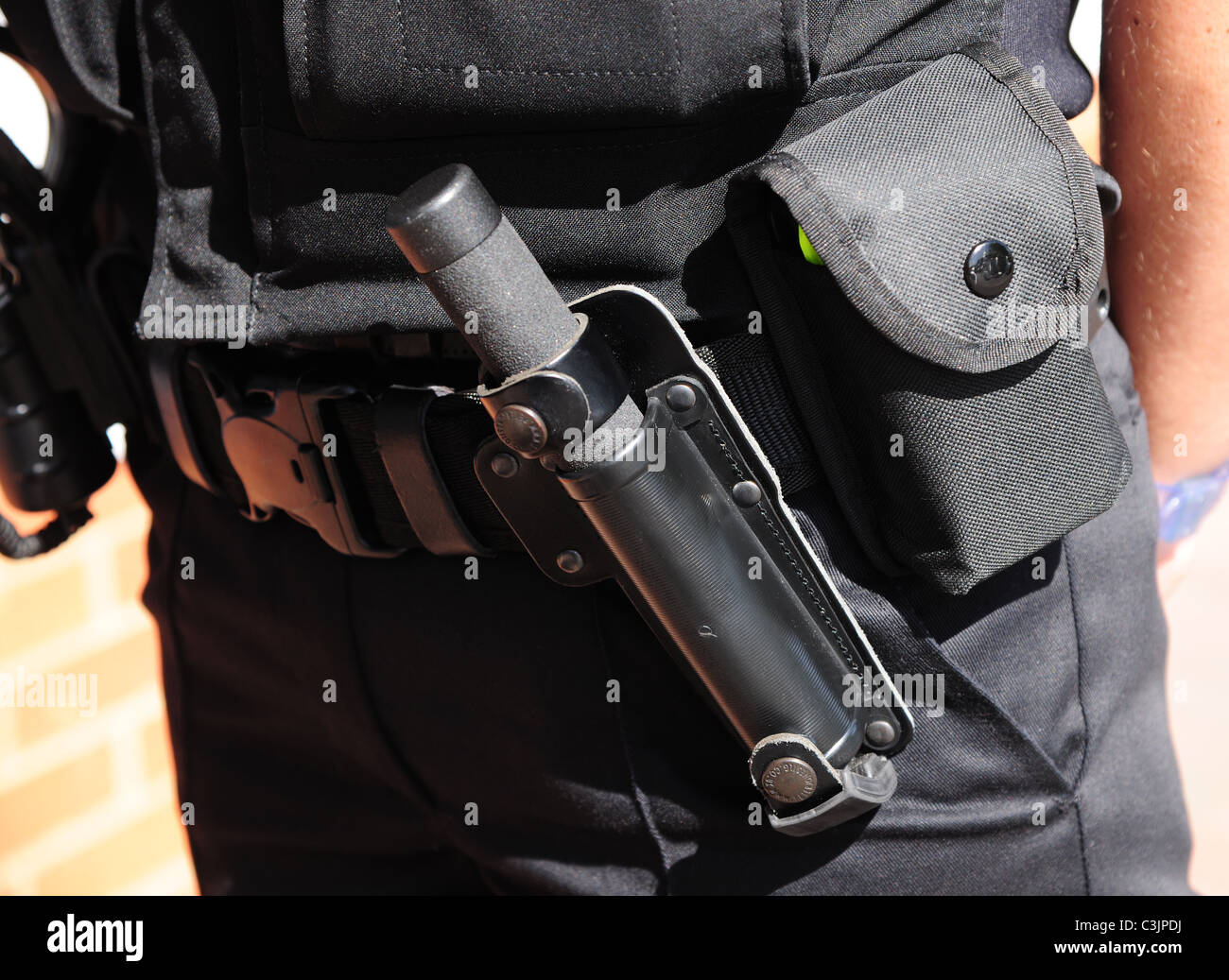 Police utility belt showing carriage of the issue police baton, called an ASP. - Stock Image