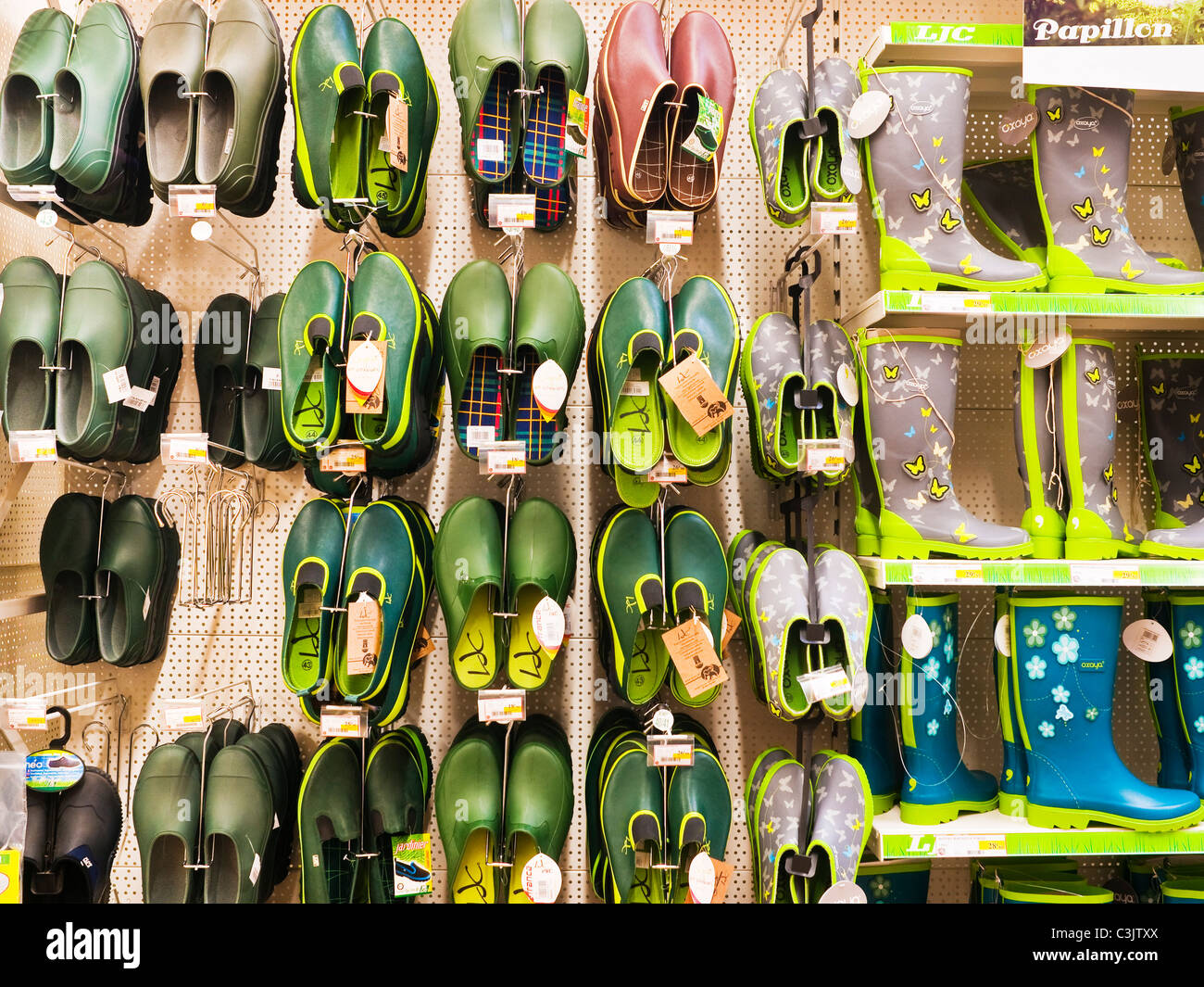 Gardening overshoes and Wellington boots display in supermarket - France. - Stock Image
