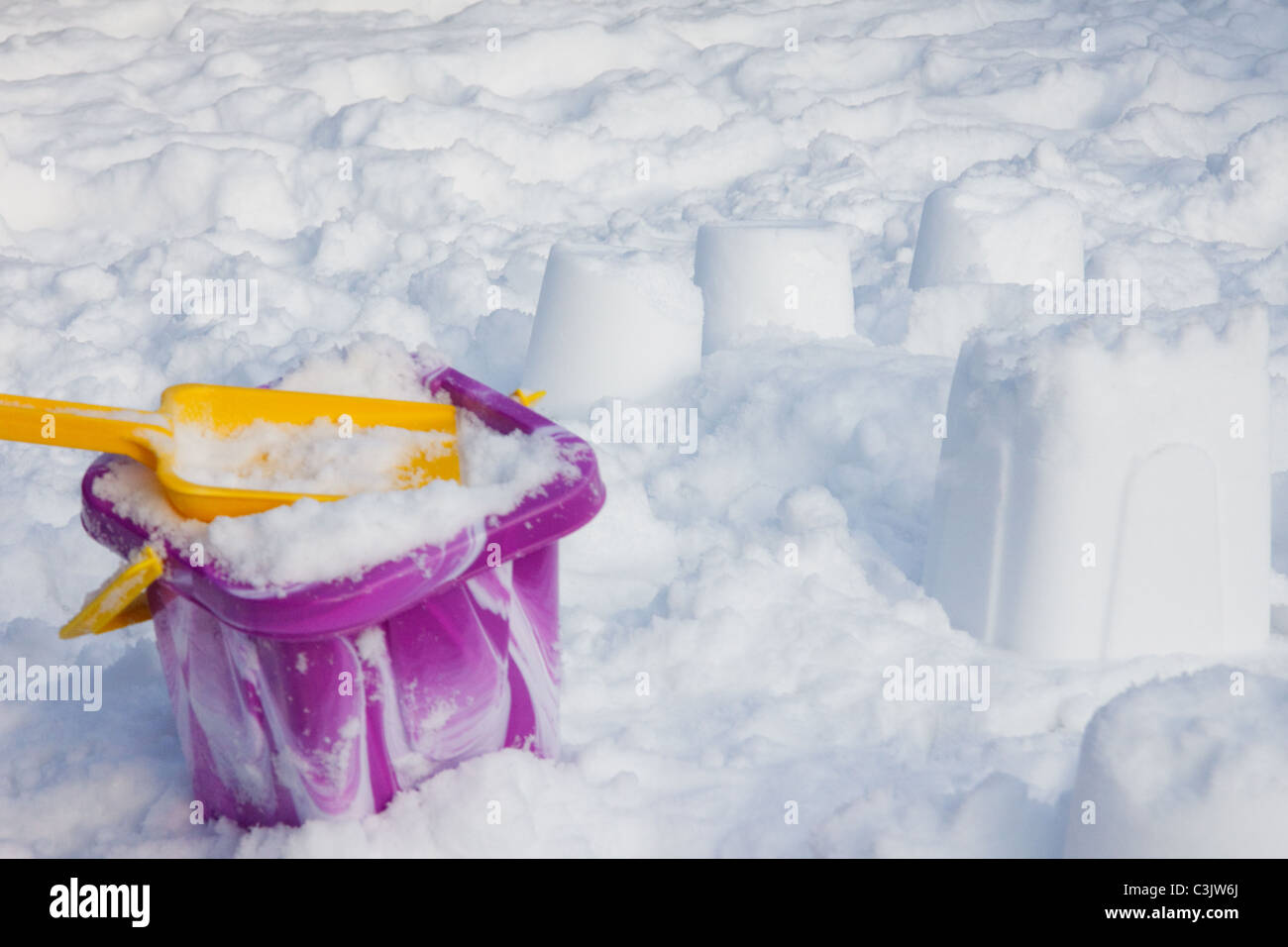 Having fun with a bucket and spade in the winter sun - Stock Image