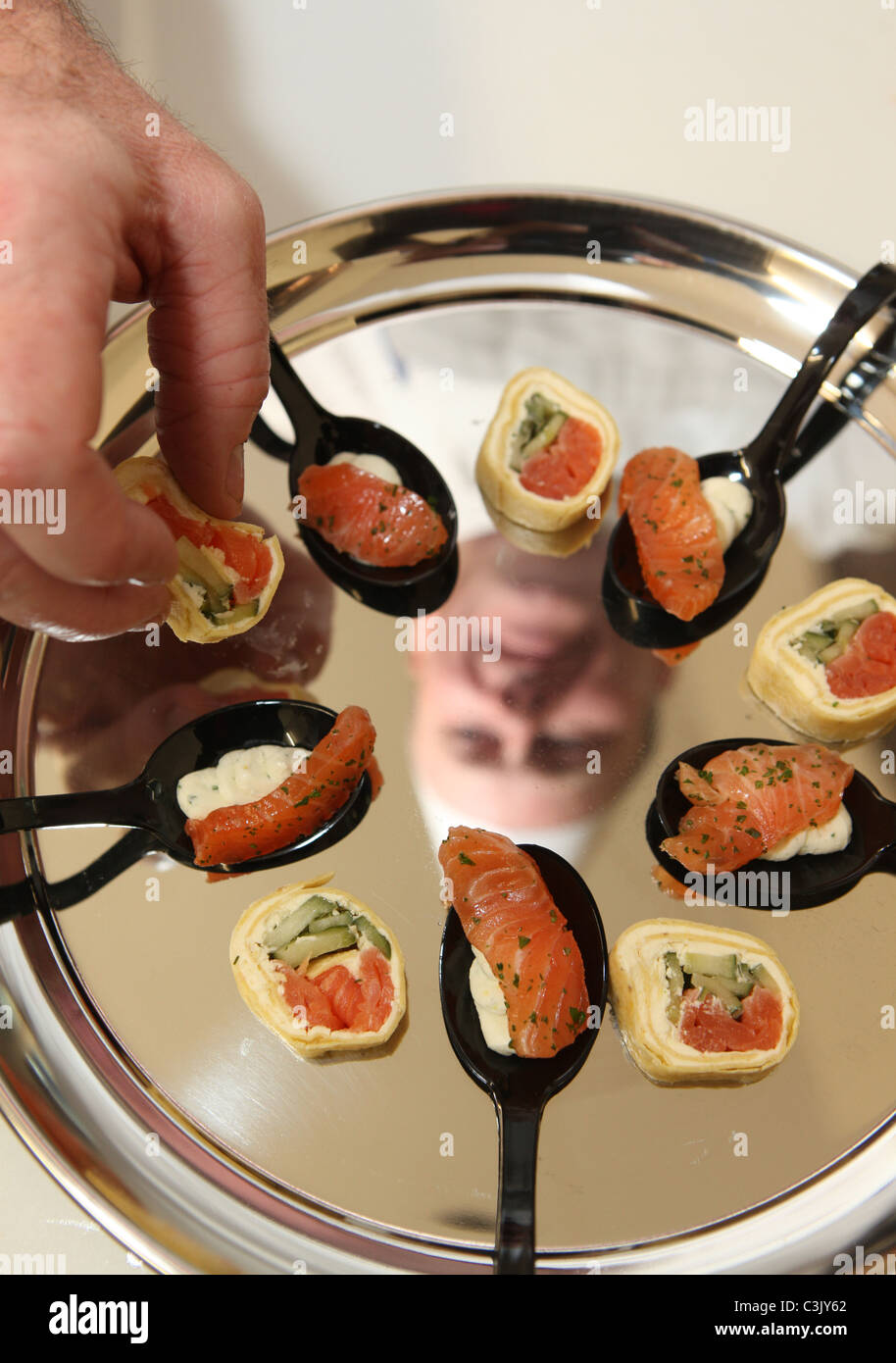 A restaurant chef preparing canapes on a silver tray - Stock Image