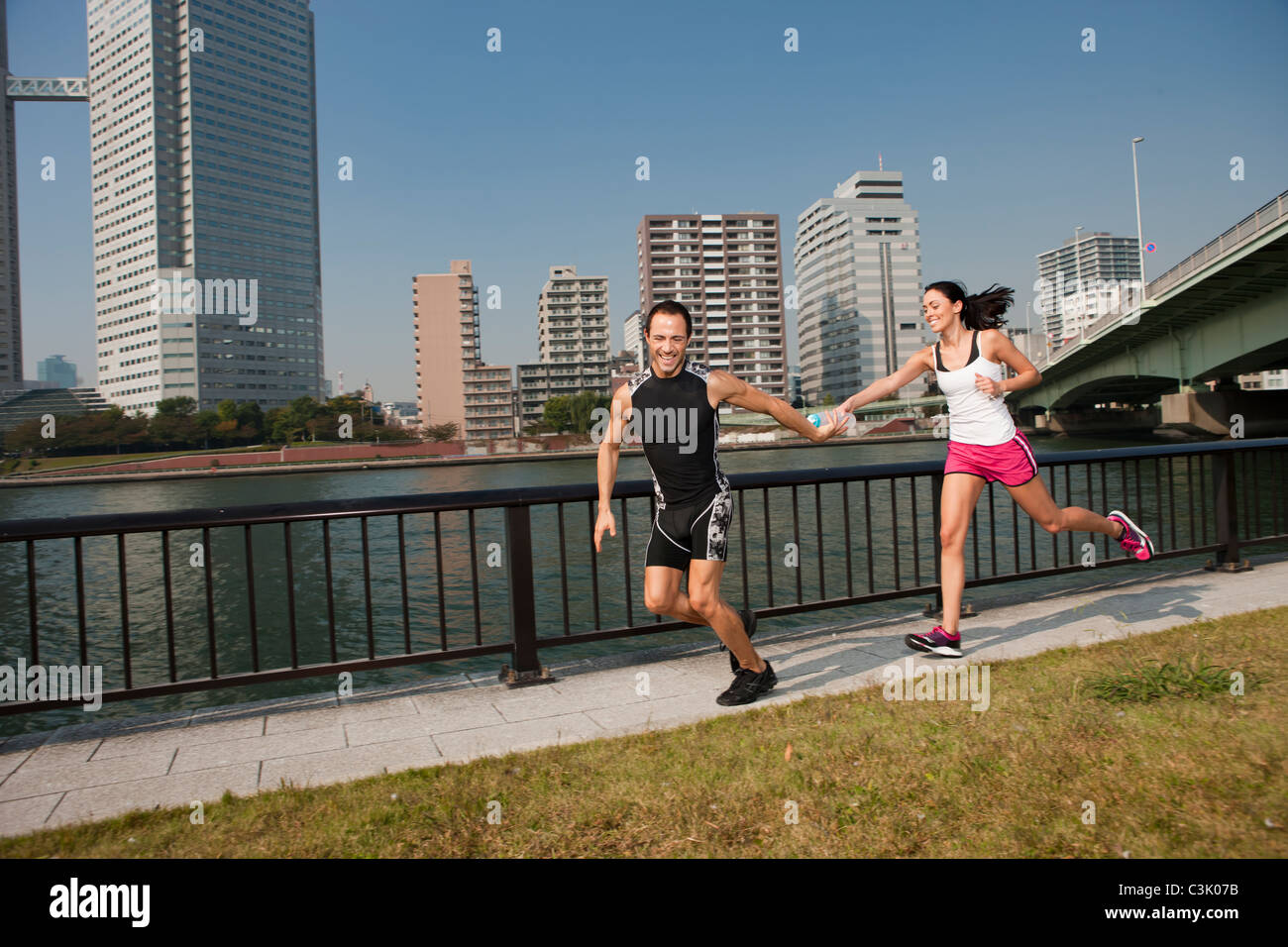 Couple hands off water bottle while running through park in city downtown. - Stock Image