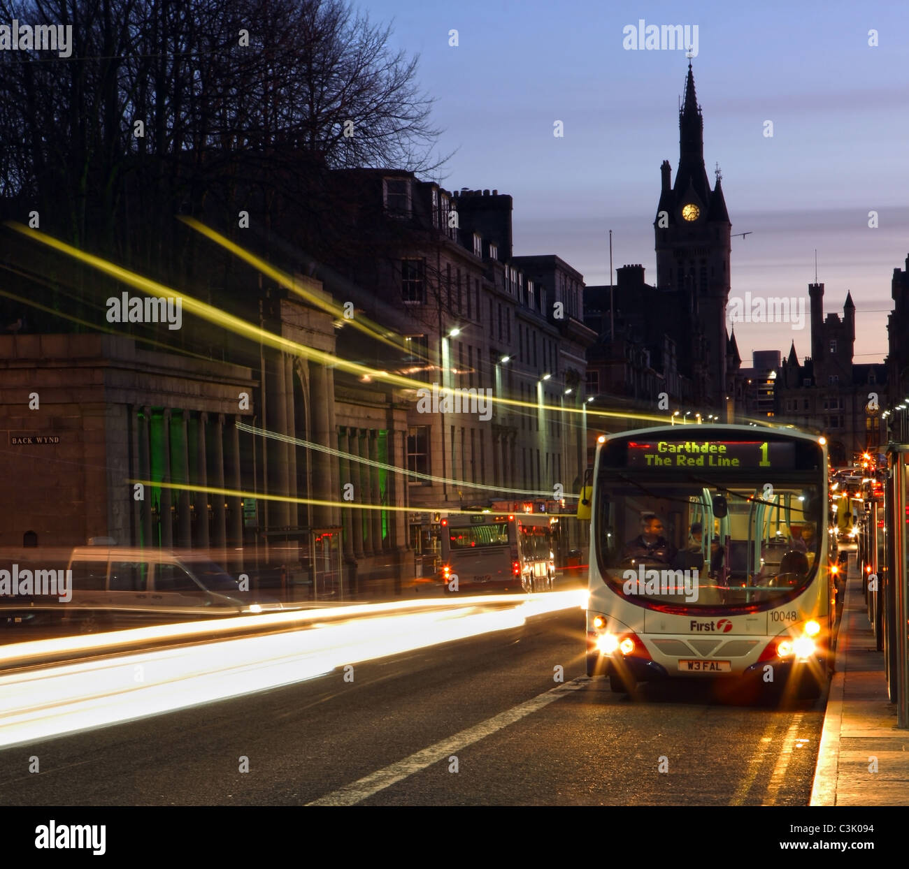 First bus in Union Street in Aberdeen, Scotland, UK at night - Stock Image