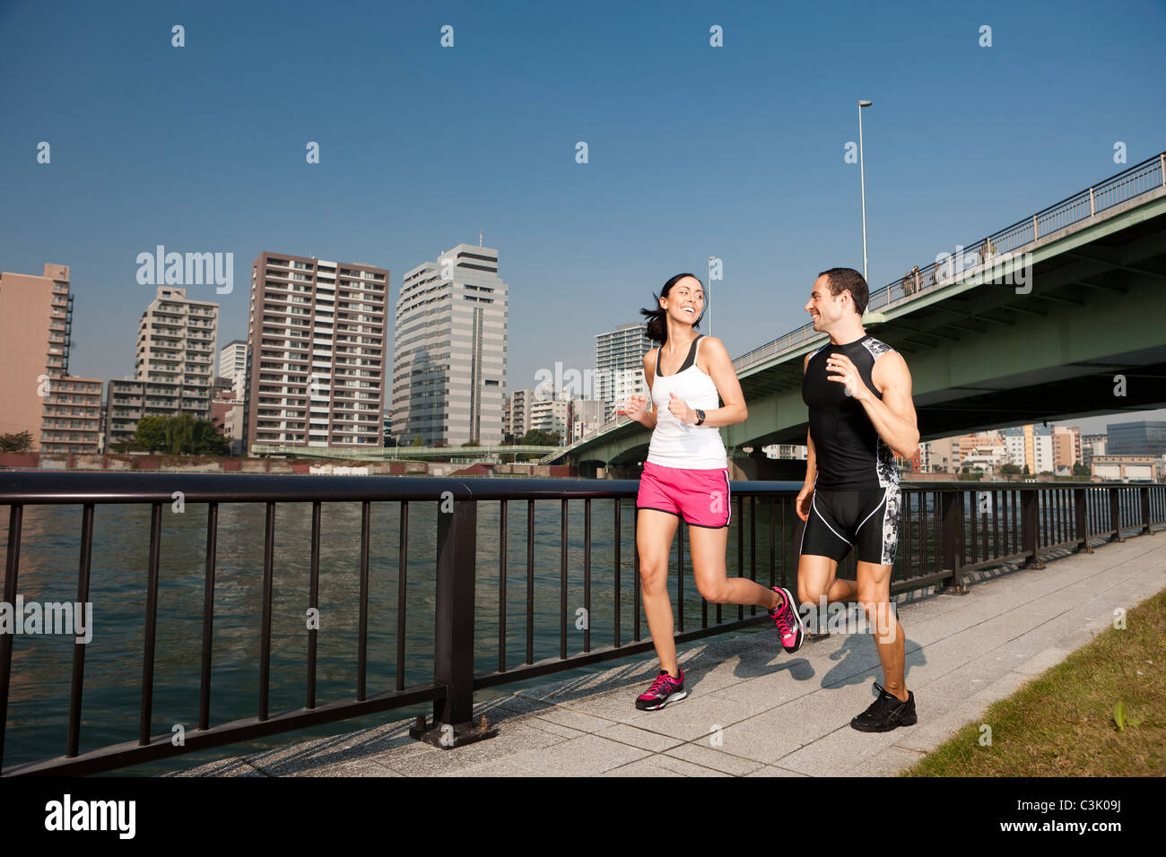 Couple smile while jogging through park in city downtown. - Stock Image