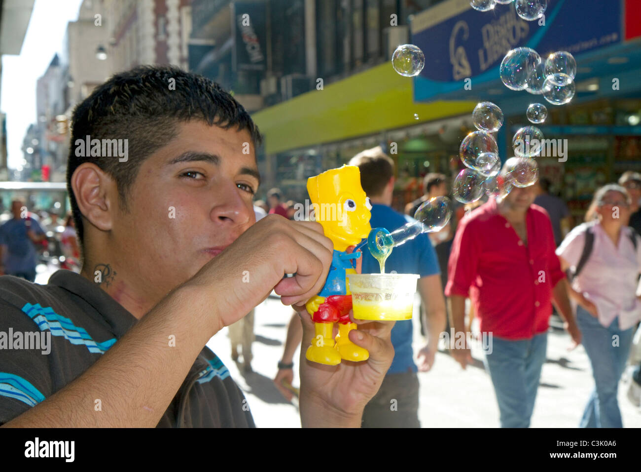 Argentine man blowing bubbles with a Bart Simpson toy along Florida Street in the Retiro barrio of Buenos Aires, - Stock Image
