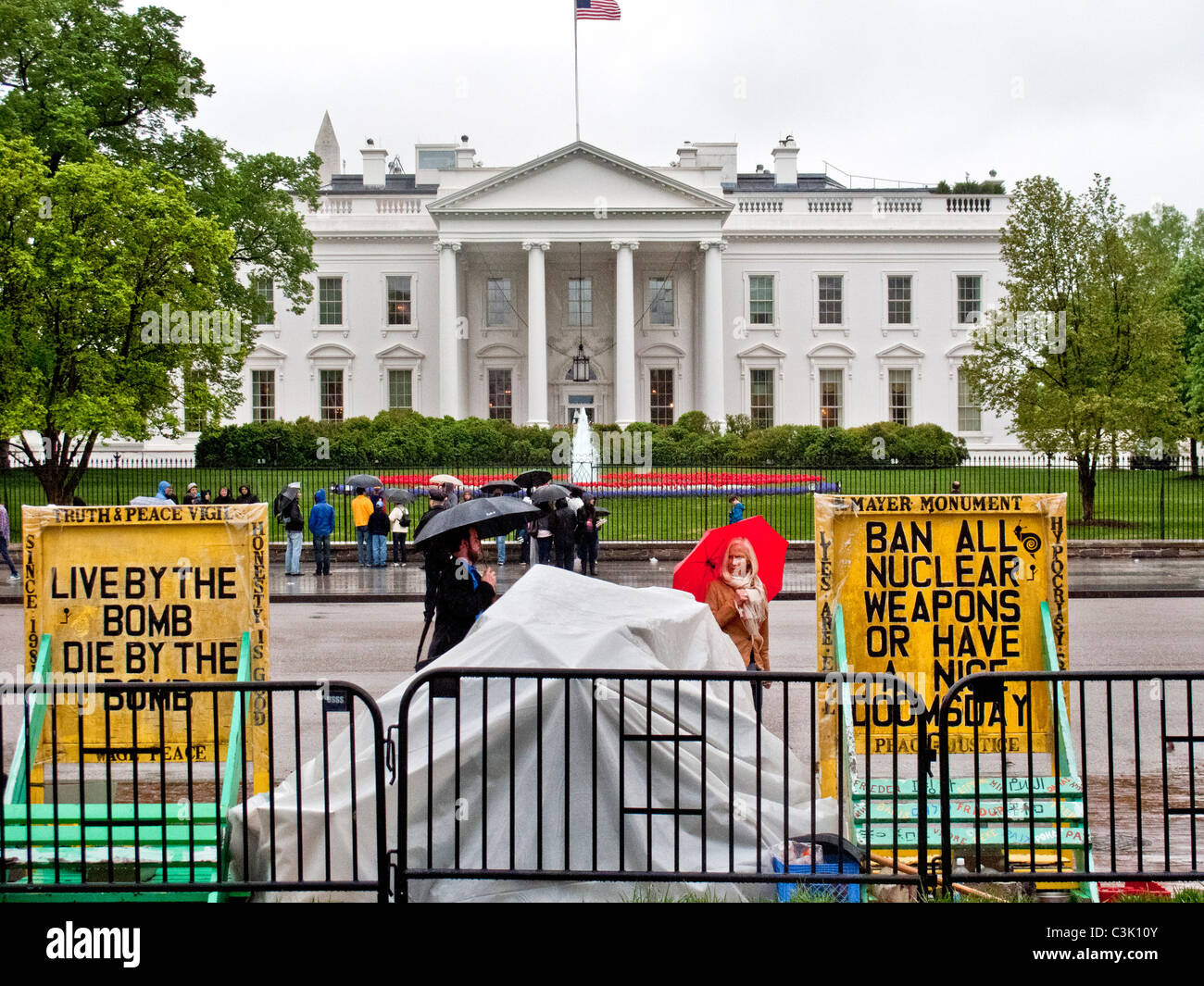 Wearing raincoats and carrying umbrellas, tourists gather outside the White House in Washington, D.C. Note anti - Stock Image