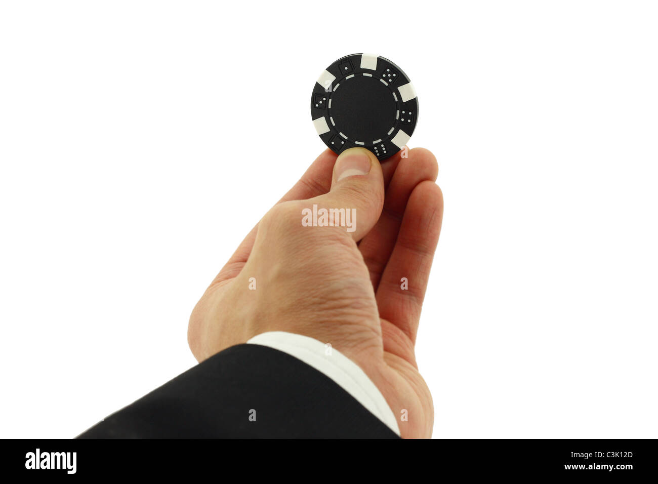Business man's hand holding a casino chip - Stock Image