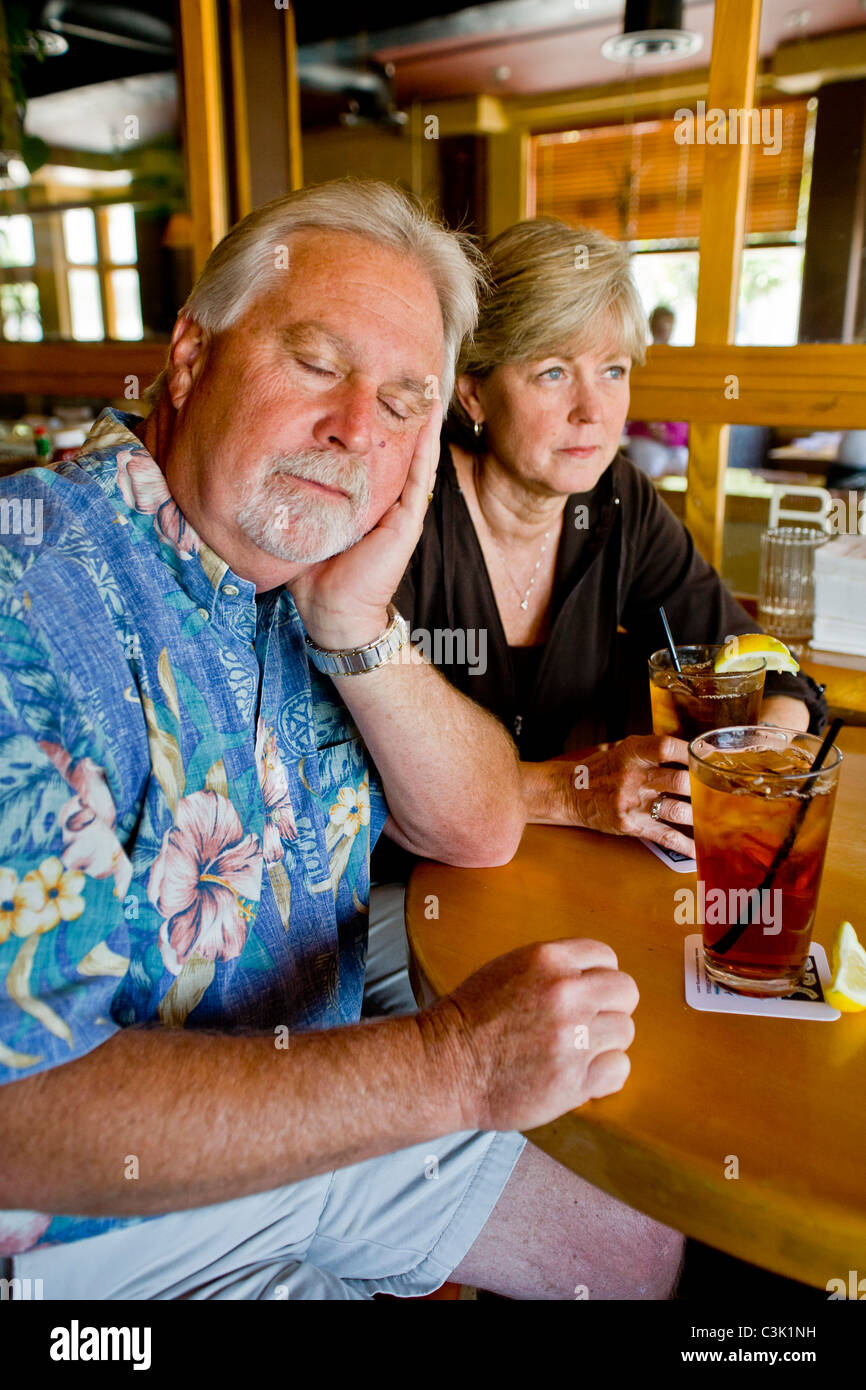A middle aged couple appeared indifferent to each others' company over iced tea together in a Long Beach, CA, restaurant. MODEL Stock Photo