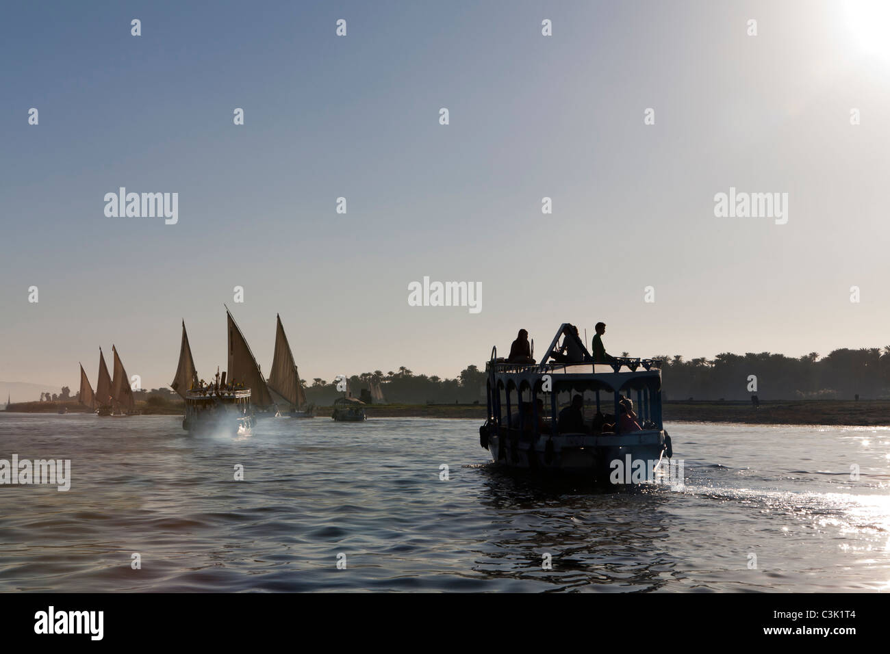 Following a Nile water taxi and several feluccas heading into the sunset on the sparkling river water, Egypt, Africa - Stock Image