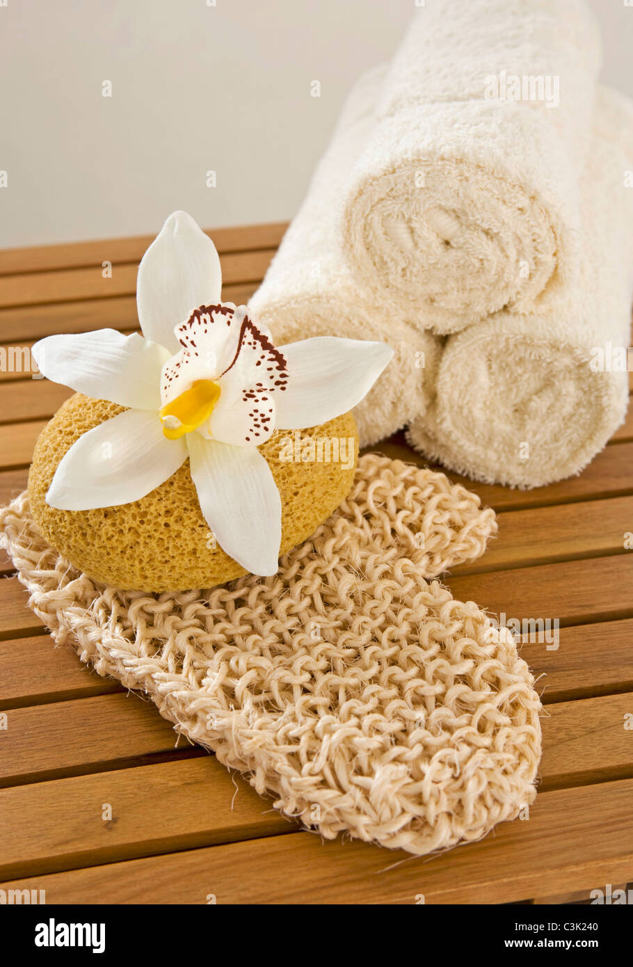 Bath sponge and rolled up towels, close up - Stock Image
