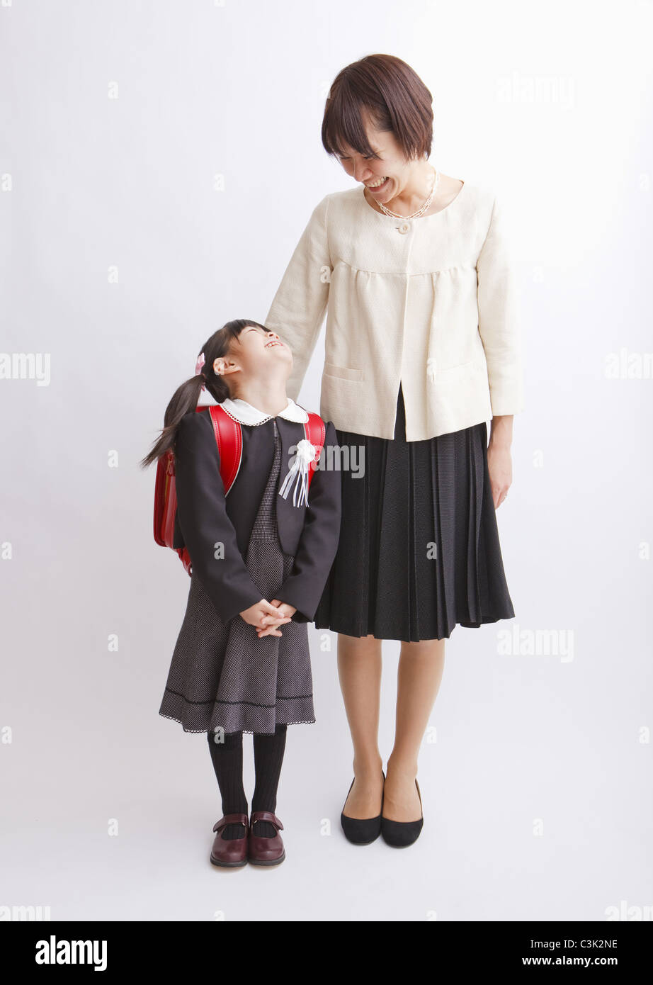 Girl carrying school bag and mother - Stock Image