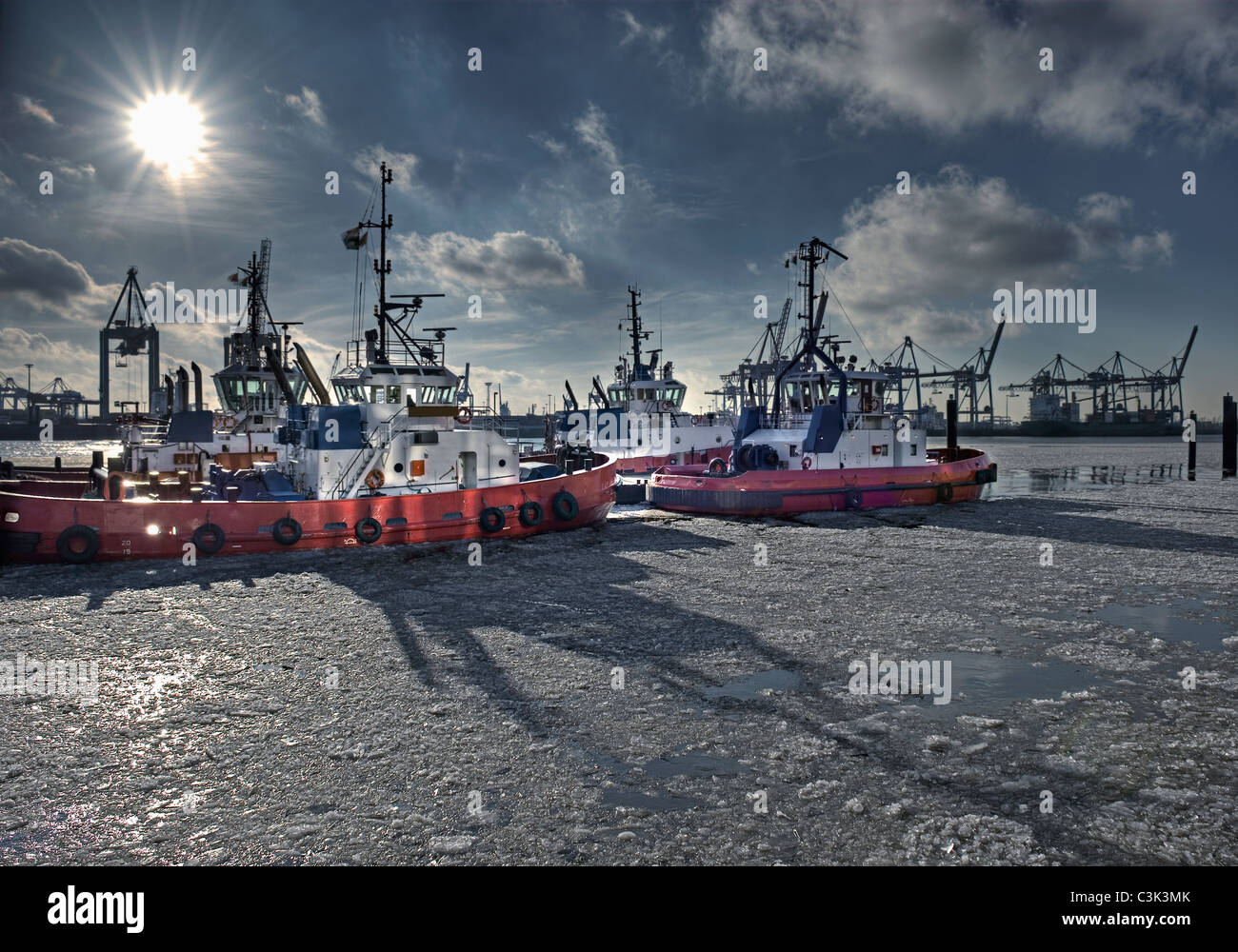 Germany, Hamburg, View of tugs moored at harbour on frozen water - Stock Image