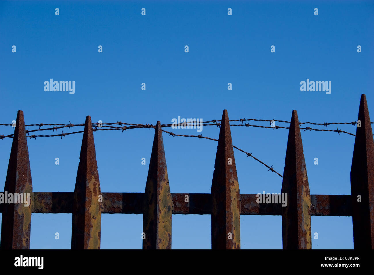 security fence rust spike top barb wire blue sky row keep out deterrent safe block sharp injury do not enter - Stock Image