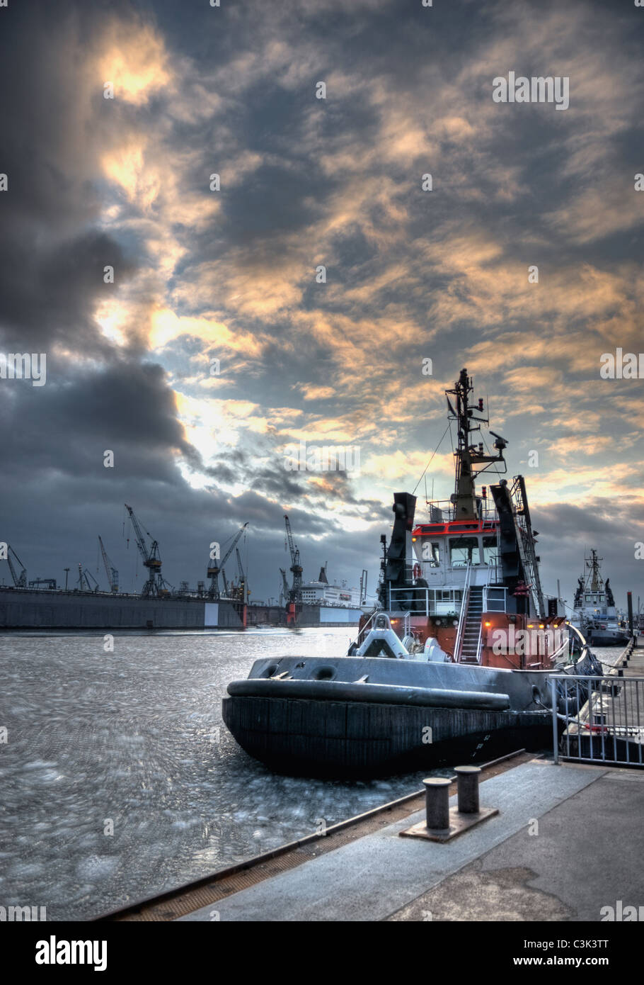 Germany, Hamburg, View of tugs at harbour in winter - Stock Image