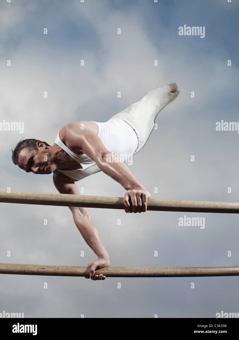 Germany, Augsburg, Young man balancing on parallel bars - Stock Image