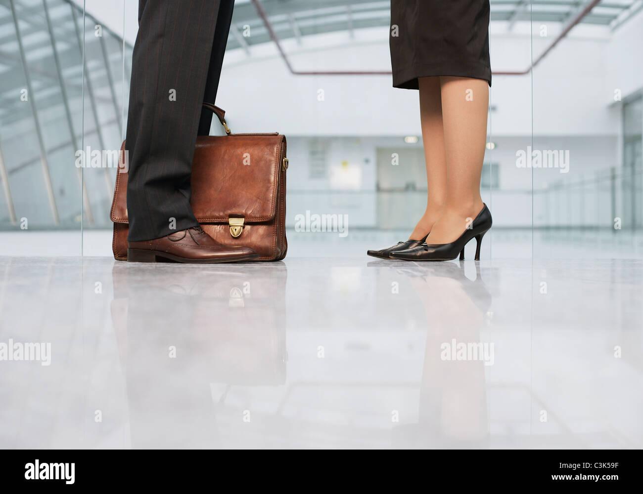 Business people standing on shiny floor - Stock Image