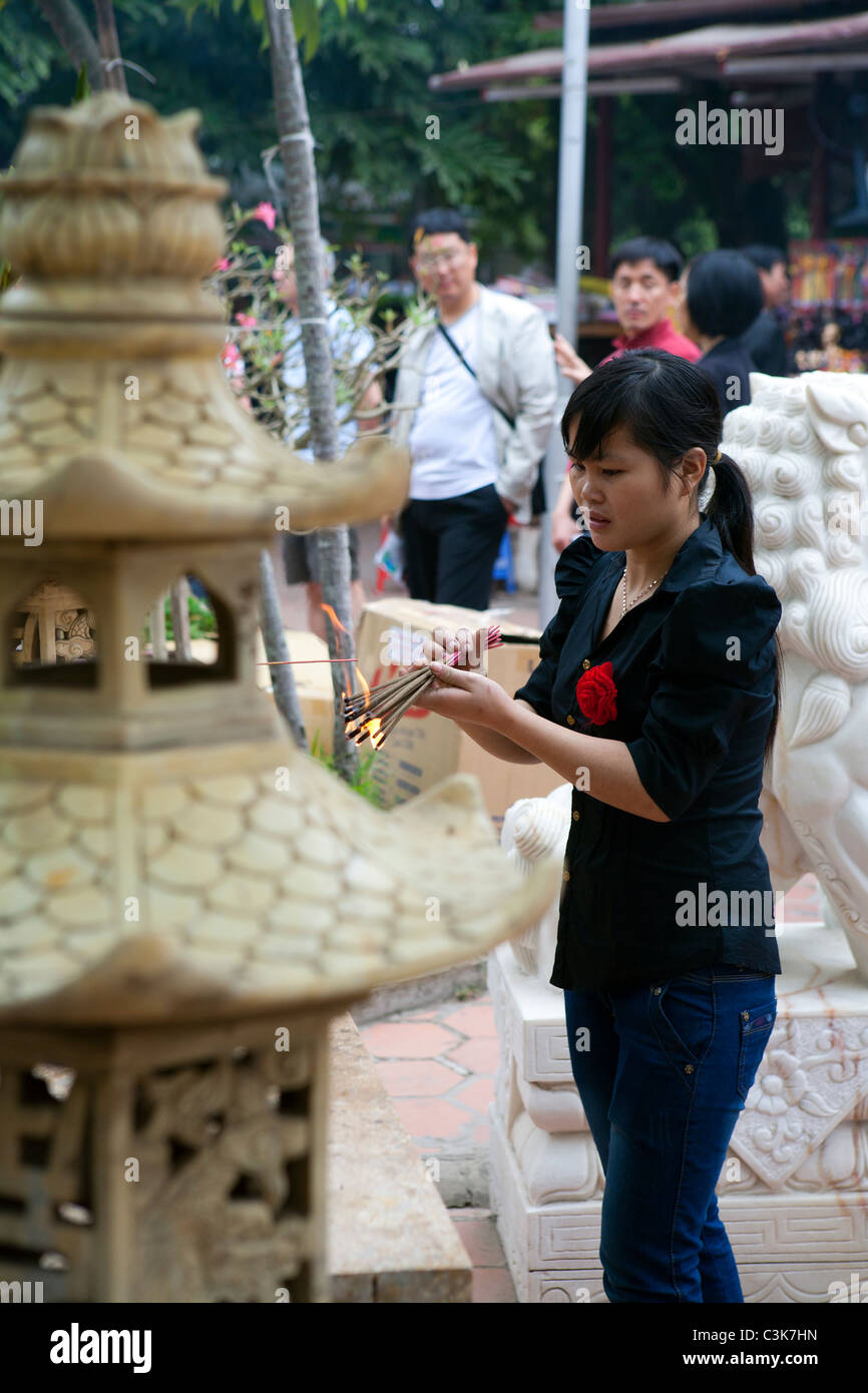Woman lighting incense sticks at Hanoi's One Pillar Pagoda Stock Photo
