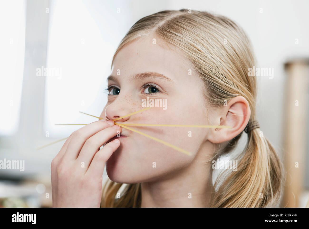 Germany, Cologne, Girl making spaghetti moustache - Stock Image