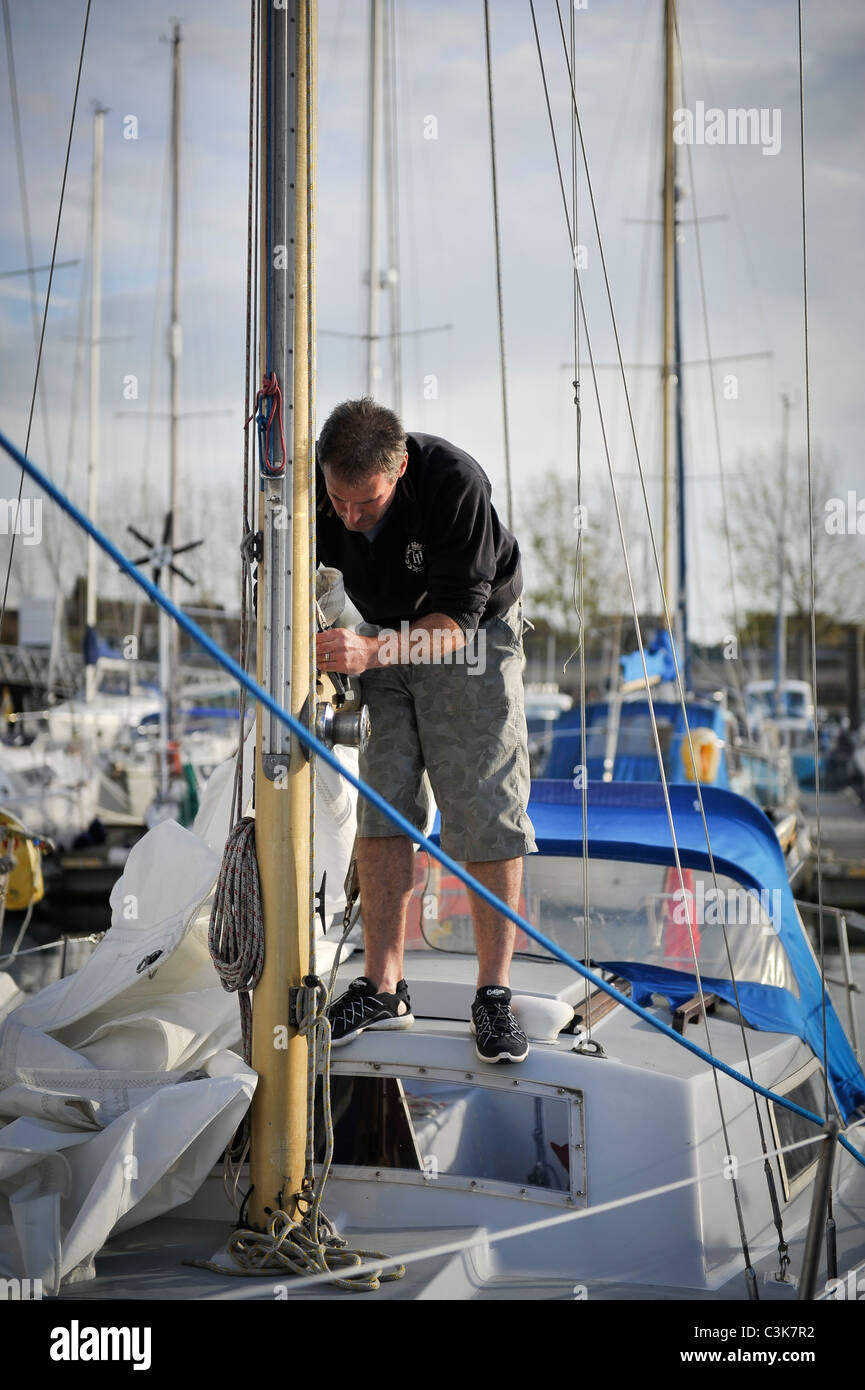 Man adjusting rigging on a sail boat - Stock Image