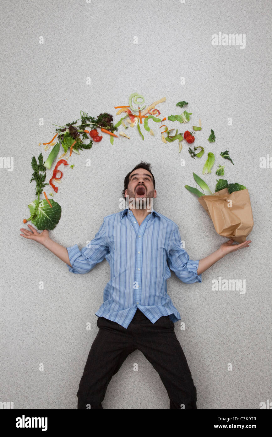 Mid adult man holding balancing vegetables with mouth open - Stock Image