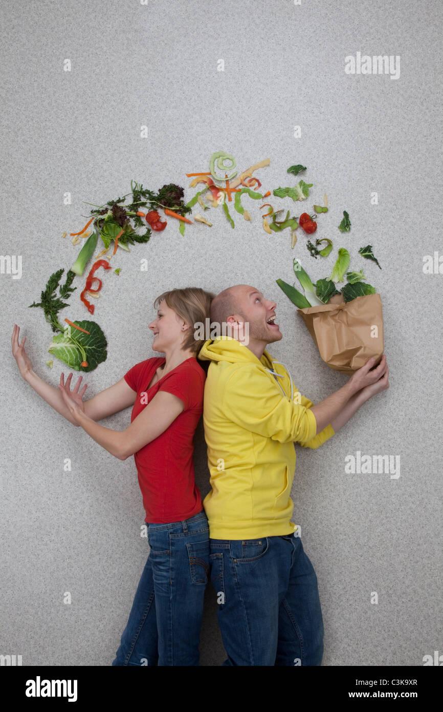 Man and woman balancing vegetables - Stock Image