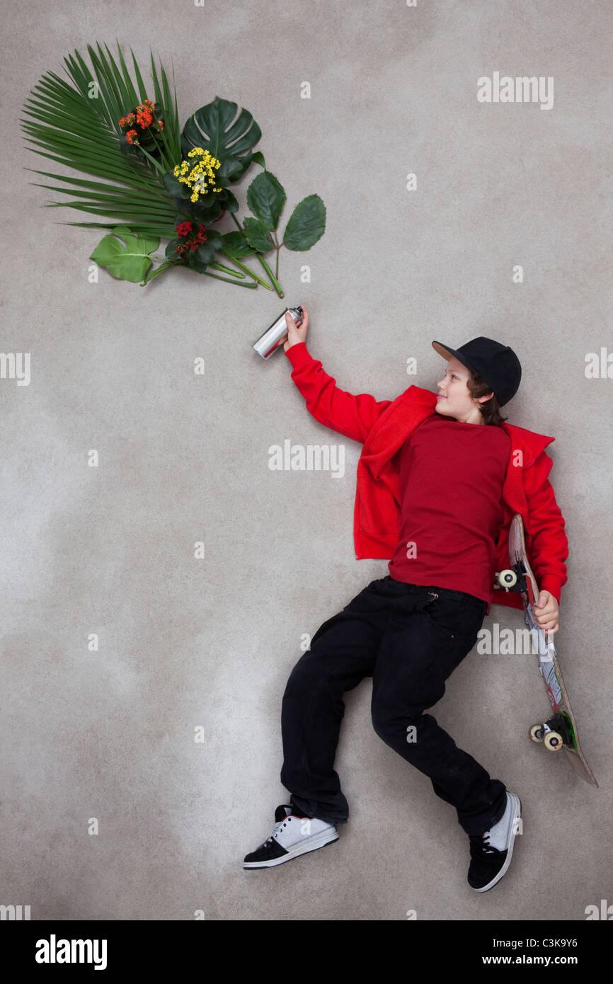 Boy spraying leaves from spray bottle Stock Photo