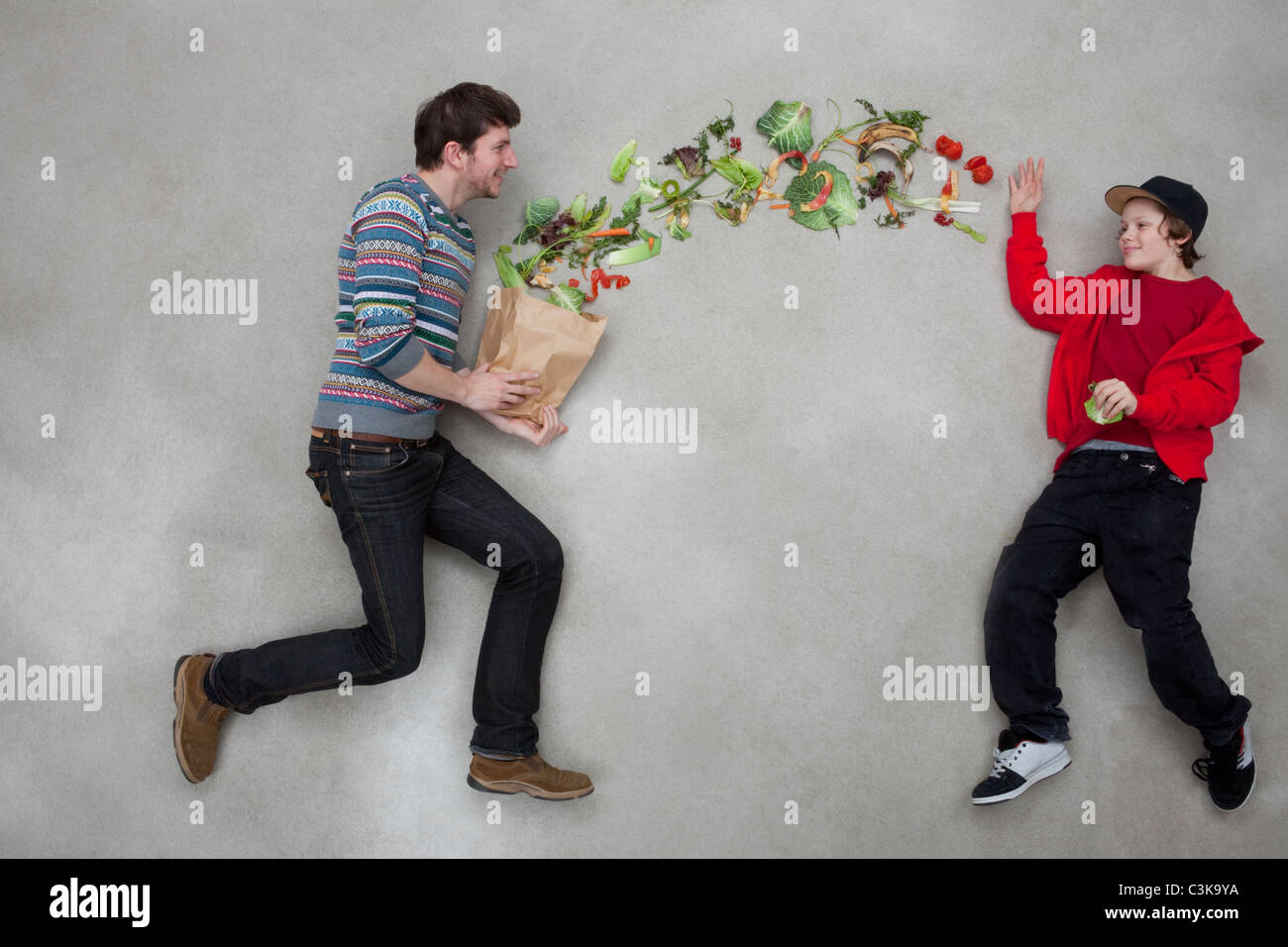 Man and boy balancing vegetables - Stock Image