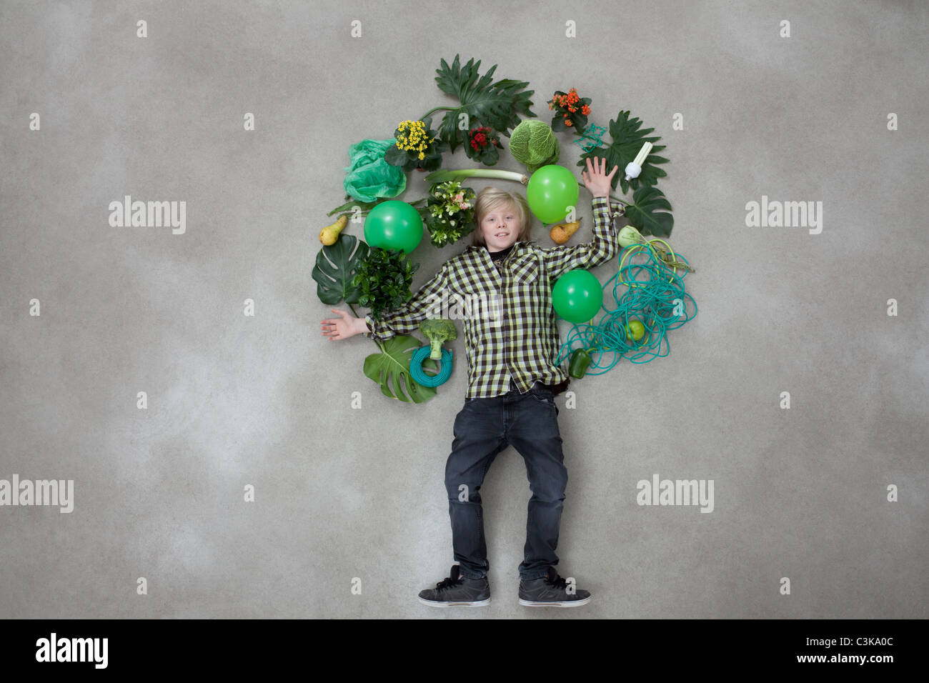 Boy forming tree shape on gray background - Stock Image