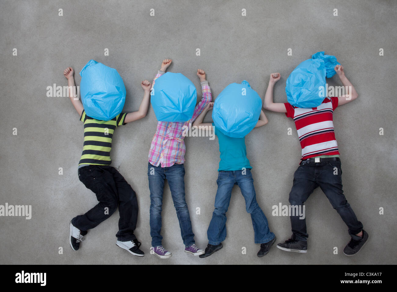 People covering their faces with plastic bags and showing ecology symbol - Stock Image