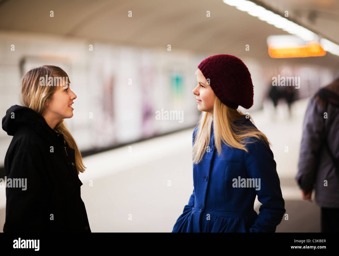 Teenage girls (14-15) talking on railway platform - Stock Image