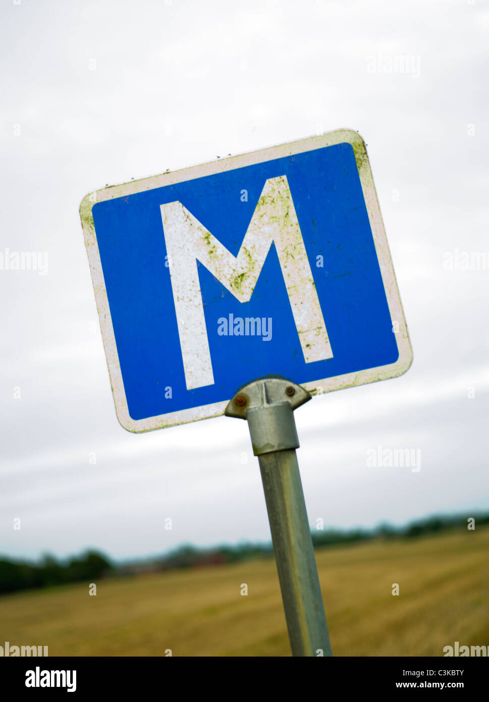 Close up of road sign with letter M - Stock Image