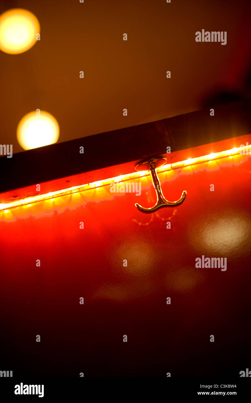 Close up of clothes hanger on red, glowing background - Stock Image