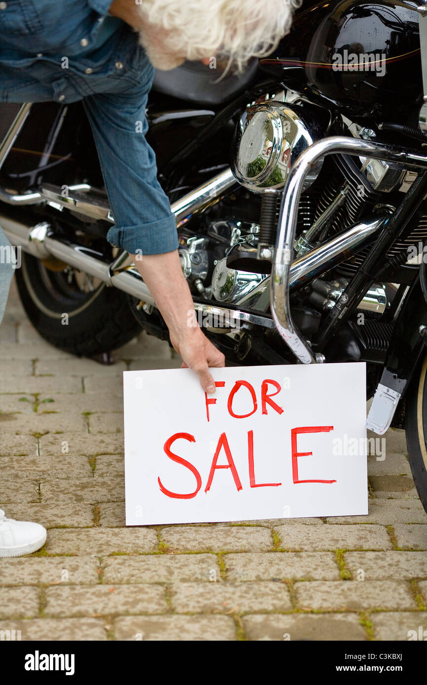 Man putting for sale sign by vintage motorbike - Stock Image