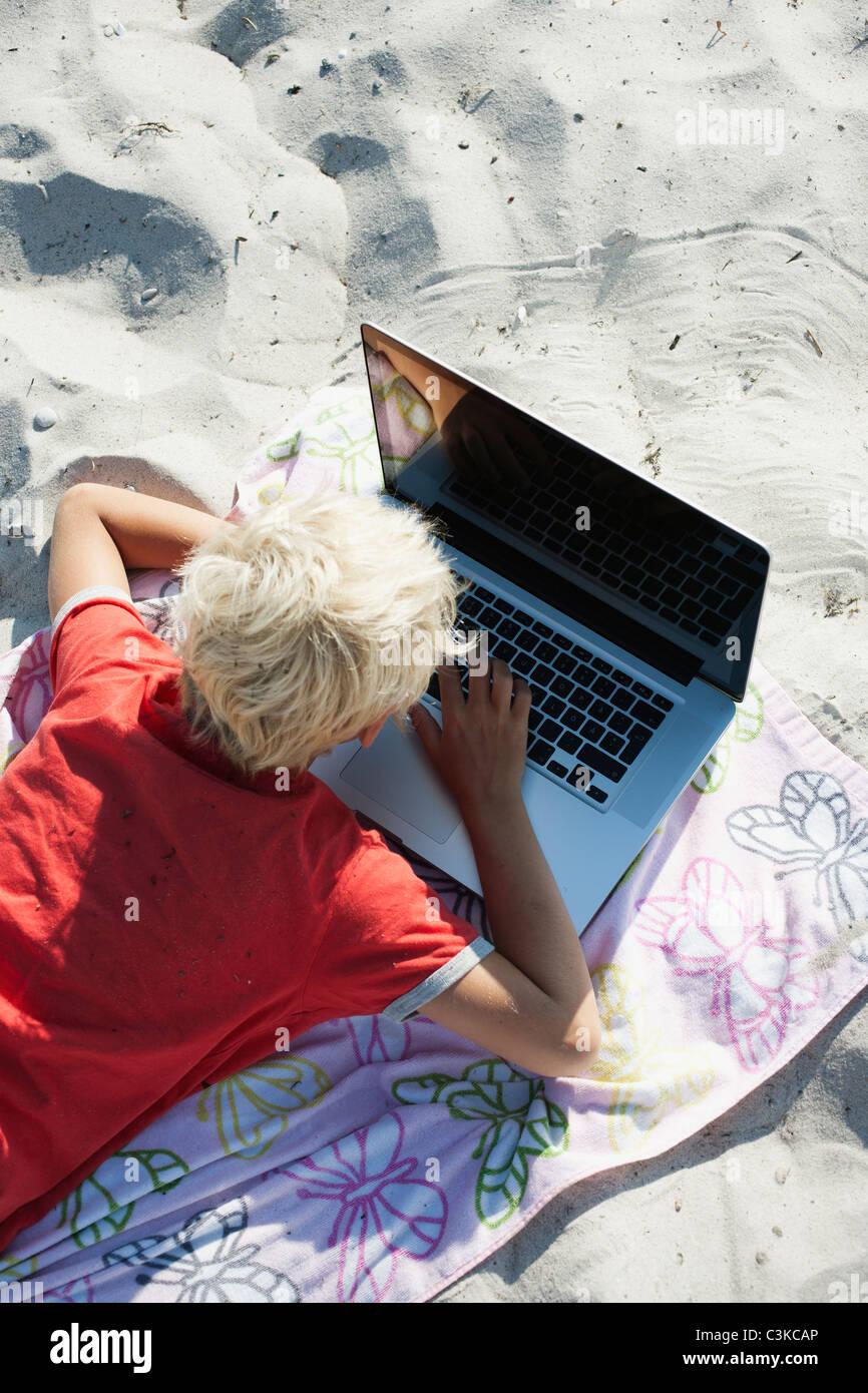 Blonde boy using laptop on beach - Stock Image