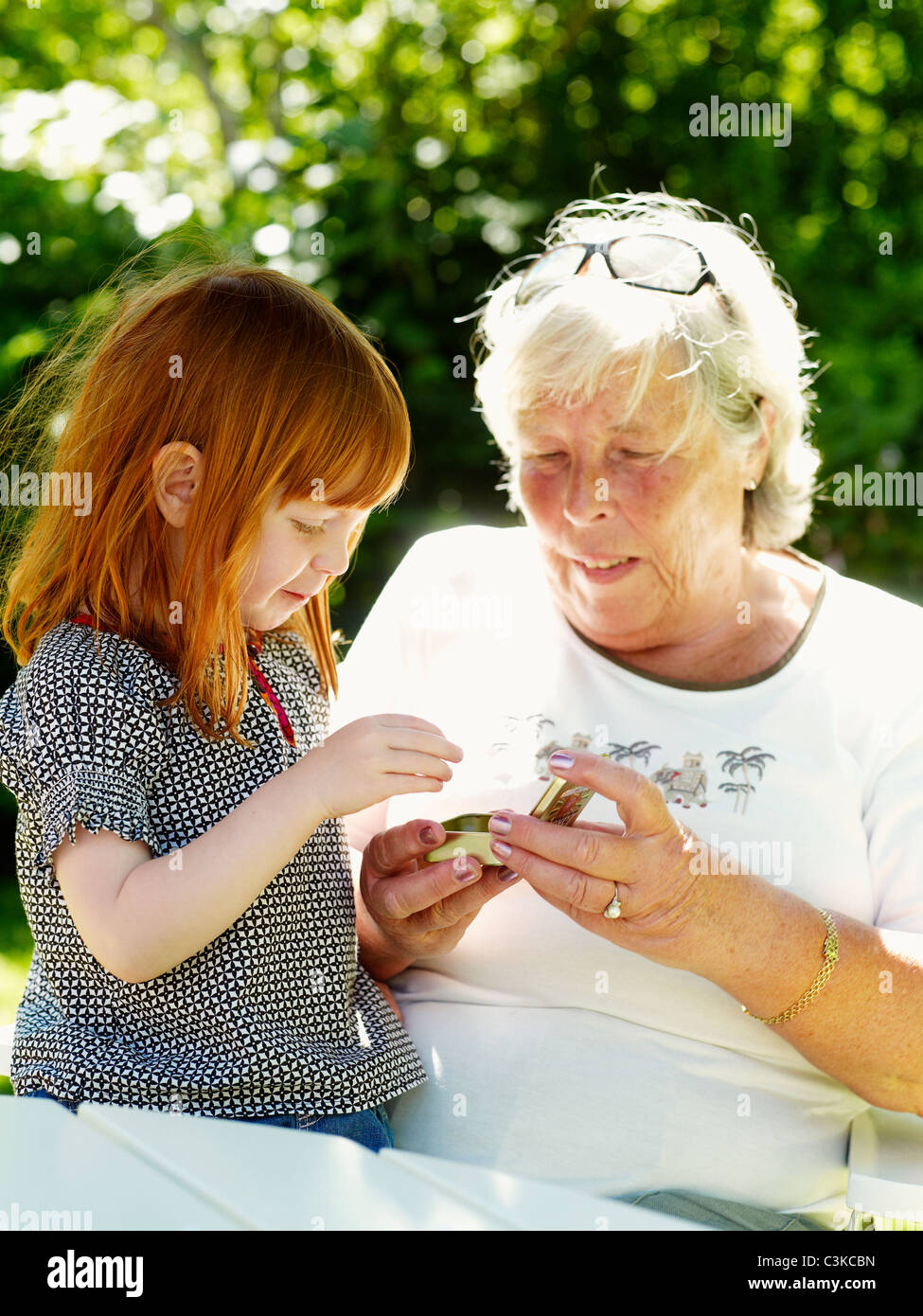 Grandmother and granddaughter eating hard candies in garden - Stock Image