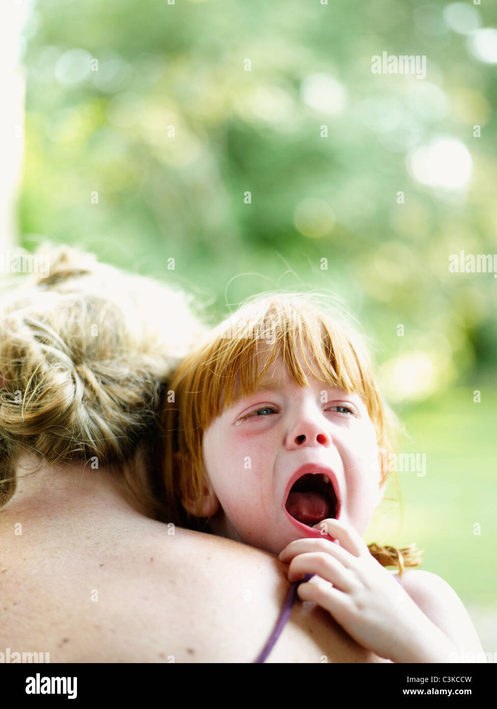 Mother consoling crying daughter - Stock Image